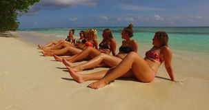 V12726 sunbathing group of young beautiful girls on white sand beach in aqua blue clear sea water and sky Stock Images