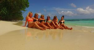 V12697 sunbathing group of young beautiful girls on white sand beach in aqua blue clear sea water and sky royalty free stock image