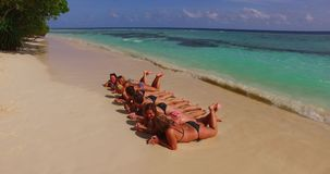 V12732 sunbathing group of young beautiful girls on white sand beach in aqua blue clear sea water and sky stock photos