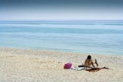 Sunbathing kobieta i Jej pies na Varigotti plaży Fotografia Royalty Free