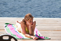 Sunbathing on a lakeside dock Stock Photography