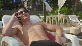 Sunbathing mężczyzna jest ubranym okulary przeciwsłonecznych opowiada na telefonie komórkowym morza i koksu sokiem Zdjęcia Royalty Free