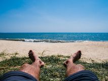 Sunbathing man on the sandy beach royalty free stock photography