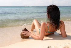 Sunbathing in Mexico. Woman sipping cocktail on the sandy tropical beach Royalty Free Stock Image