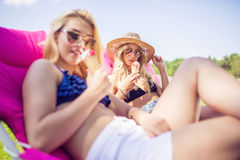 Sunbathing on the pink sunbed. A photo of young, beautiful women relaxing on pink sunbed with her friend and eating ice cream Stock Photos