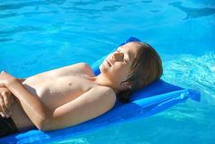 Sunbathing in Pool. Teen boy lying wet on an air mattress in the pool on a sunny day Stock Images