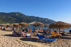 Sunbathing sandy Mediterranean beach Corfu, Greece. Corfu, Greece - August 31, 2014: Sunbathers relax on a sandy beach on the Greek island of Corfu Stock Images