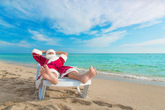 Sunbathing Santa Claus relaxing in bedstone on beach - Christmas stock image