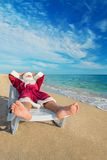 Sunbathing Santa Claus relaxing in bedstone on tropical beach Royalty Free Stock Photo