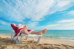 Sunbathing Santa Claus relaxing in bedstone on tropical beach royalty free stock photos