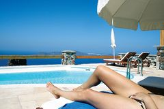 Sunbathing On Santorini Island. Woman sunbathing near the pool at a resort on Santorini Island in Greece.  Woman is shown from the waist down only Stock Photos
