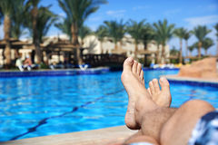 Sunbathing by swimming pool. Sunbathing by the hotel tourist resort swimming pool, mans legs lying down on a sunlounger looking over the water Stock Images