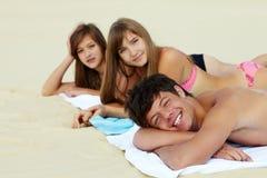 Sunbathing on vacation. Portrait of three teenage friends lying on the beach and sunbathing Stock Images