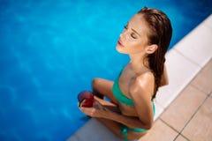 Sunbathing woman enjoying cocktail. And swimming pool royalty free stock image