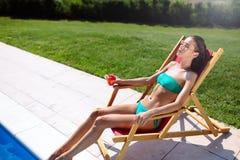 Sunbathing woman enjoying cocktail. And swimming pool royalty free stock photos