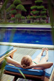 The sunbathing woman near a swimming pool Stock Photo
