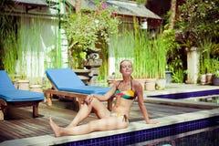 The sunbathing woman near a swimming pool Royalty Free Stock Photo