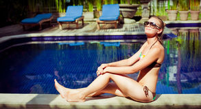 The sunbathing woman near a swimming pool Stock Photos