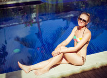 The sunbathing woman near a swimming pool Royalty Free Stock Photo