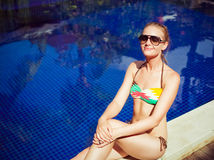 The sunbathing woman near a swimming pool Royalty Free Stock Photos