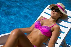 Sunbathing woman at poolside. The beautiful woman in bikini with hat and sunglasses is sunbathing and enjoying at poolside on blue background Royalty Free Stock Images