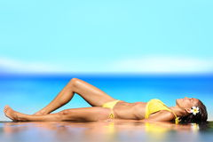 Sunbathing woman relaxing under sun in luxury. Woman lying on her back on wet sand in front of the ocean at the seaside sunbathing in her bikini with a happy Royalty Free Stock Images