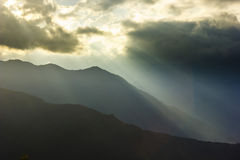 Sunbeam above mountains at sunset. With clouds on sky and shades on earth Stock Photo