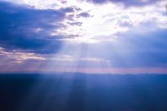 Sunbeam through clouds on blue sky. stock photo