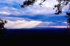Sunbeam through clouds on blue sky. stock photos