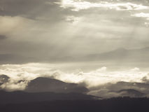 Sunbeam through clouds over mountain Royalty Free Stock Images