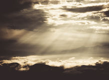 Sunbeam through clouds over mountain Stock Photography