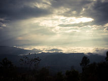 Sunbeam through clouds over mountain Royalty Free Stock Photo