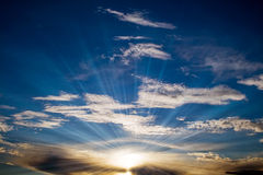Sunbeam in cloudy blue sky over it Royalty Free Stock Photography