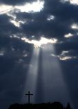 Sunbeam and cross. Dramatic sky with sunbeam and silhouette of cross Stock Image