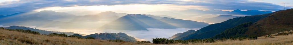 sunbeam för berg för gryningogenomskinlighet disig arkivfoto