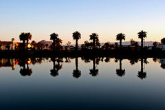 Sunbeam Lake Reflection. The placid waters of Sunbeam Lake, near El Centro, California, reflect the palm trees and sky like a mirror Royalty Free Stock Photos