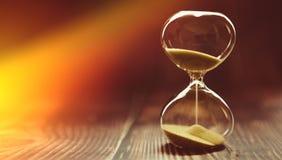 Sunbeam penetruje hourglass, symbolizujący początek czas lub definitywny czas Zegar na drewnianym tle obrazy royalty free