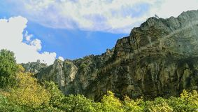 A Sunbeam Shooting Through Canyon. A rocky wall with giant clouds overhead and a sunbeam shooting through Little Rock Canyon, UT, US Royalty Free Stock Image