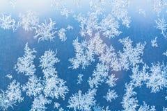 Sunbeam spots and frosty pattern on window pane Stock Photo