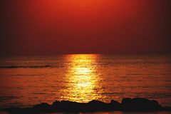 Sunbeam during sunset casting long yellow bright golden shimmering ray of light over the ocean. Ko Lanta, Thailand royalty free stock photo