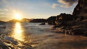Sunbeam. A sunbeam that winds the sea at sunset, shining the rocky coast of Tellaro Stock Photo