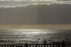 Sunbeaming till och med moln på havet Royaltyfri Bild