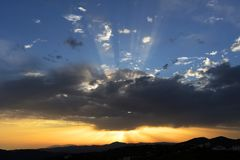 Sunbeams behind clouds, spreading out behind the hills of Sedella, Spain. Stock Photography