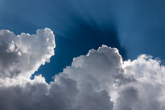 Sunbeams behind cumulus clouds Royalty Free Stock Images