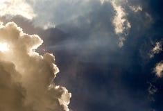 Sunbeams break thorugh a dense and gray cumulus stock images