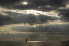 Sunbeams breaking through cloud cover, a sailboat sailing on a lake near Amsterdam. stock photography