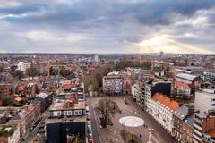 Sunbeams breaking through the cloud deck, with a panorama of Leuven, Flanders, Belgium. stock image