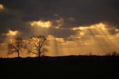 Sunbeams breaking through a dark sky. stock images