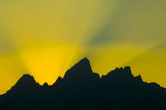 Sunbeams burst over mountains at sunset Royalty Free Stock Photos