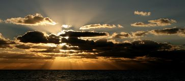 Sunbeams in the clouds. Sunset over the ocean Stock Photos